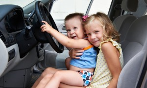 Funny young children are driving big cars